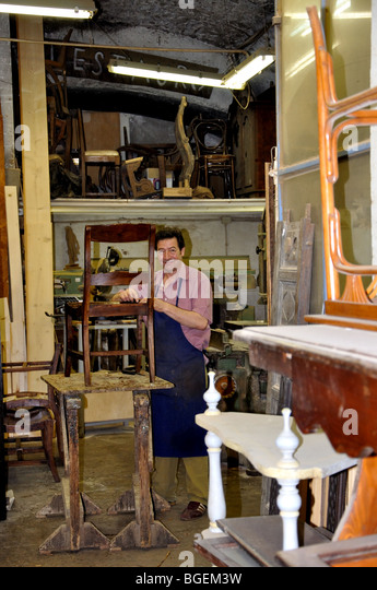 Elegant Craftsman Works On A Chair In A Furniture Repair Shop, Rome, Italy   Stock