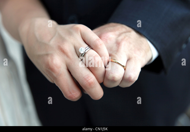 bride and groom holding hands and showing wedding rings close up stock image