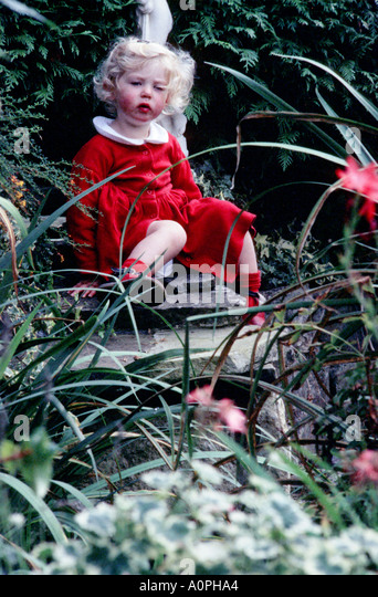 Little Blond Haired Girl Dressed In Red Leaning Against A Garden Statue  Whilst Sitting By A