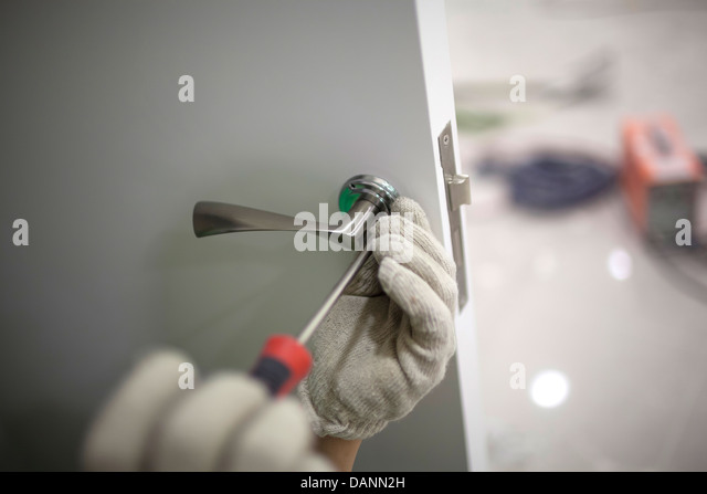workers are installing a door lock with a screwdriver - Stock Image & Fix Door Stock Photos \u0026 Fix Door Stock Images - Alamy