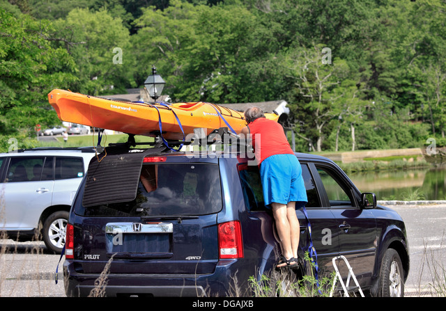 Man Securing Kayak To Car Roof Long Island New York   Stock Image