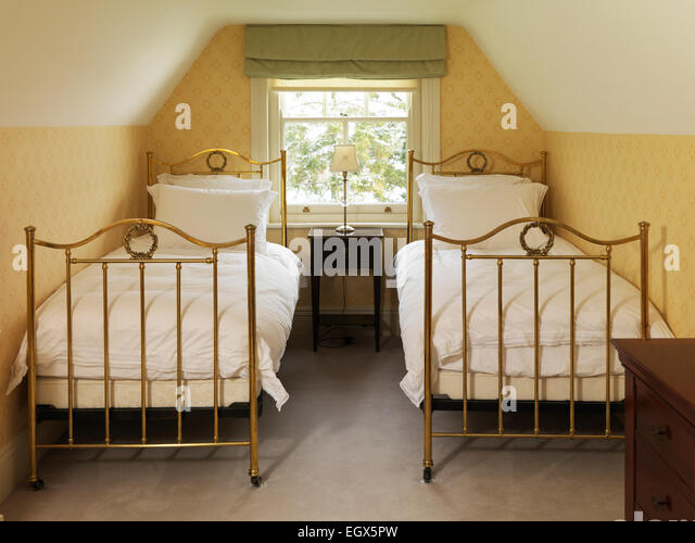 two brass beds in attic bedroom uk home stock image - Brass Beds