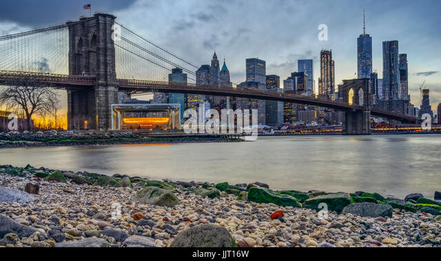 Manhattan Bridge and NYC Skyline at night with reflection of  the skyline on East River - Stock Image
