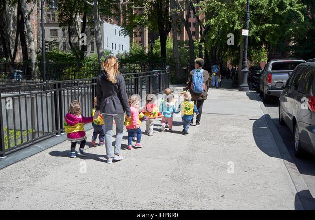 women walking preschool children on walking rope tudor city new york city usa - Stock Image