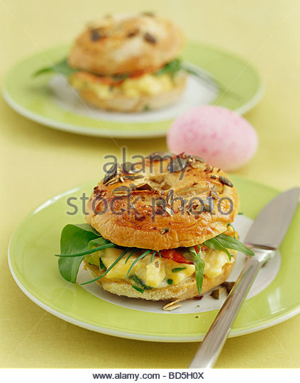 Scrambled egg, herbs and bacon in bagel - Stock Image