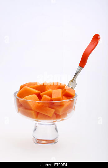 ... Papaya pieces in fruit salad with fork in glass bowl - Stock Image