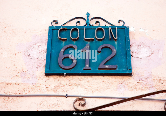paint spattered decorative blue sign with bronze house numbers mounted to pink plaster house wall oaxaca - Decorative House Numbers