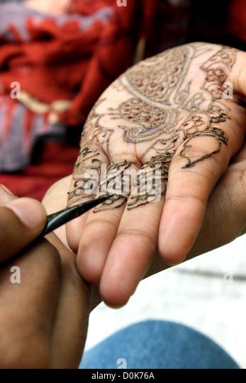 Apply Mehndi Hands : Drawing henna on hand stock photos