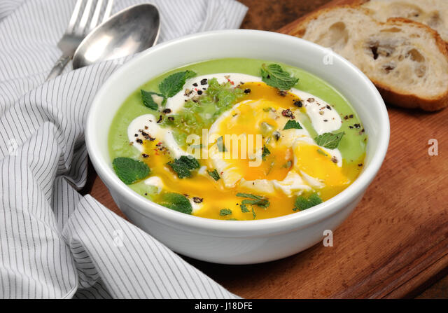 Pea puree soup with poached egg, sour cream, mint leaves seasoned with ...