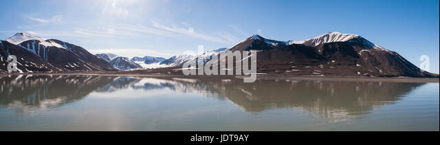 A panoramic view of Mushamna in Spitzbergen with smooth water reflecting the bare rock and ice of the hills behind. - Stock Image