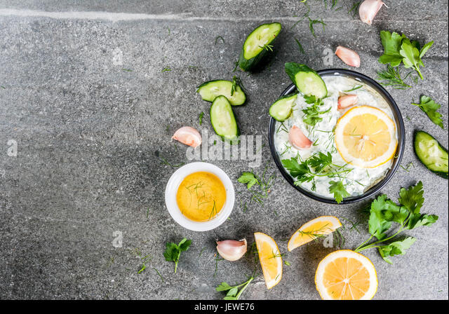 Traditional Caucasian and Greek food. Sauce tzatziki with ingredients - cucumber, lemon, parsley, dill, garlic. - Stock Image