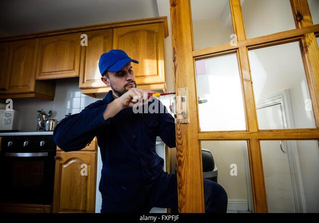 Man Fixing The Door Handle With Screwdriver   Stock Image