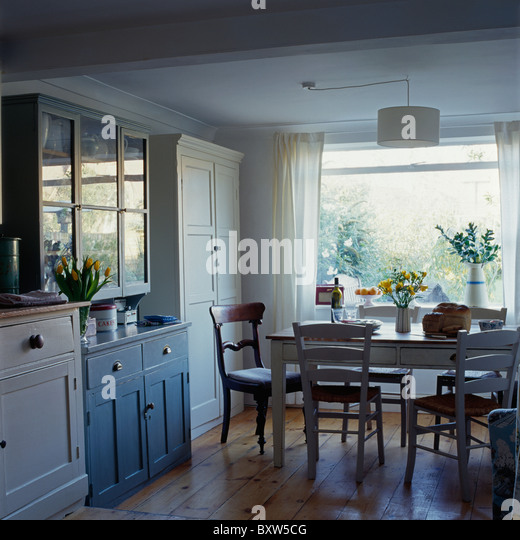 Antique Table And Chairs In Small Dining Room With Blue Fitted Dresser Wooden Flooring