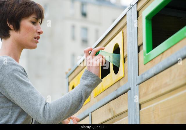 Woman placing plastic bottle in recycling bin - Stock Image