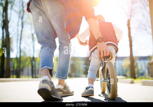 Father teaches son ride bike - Stock Image