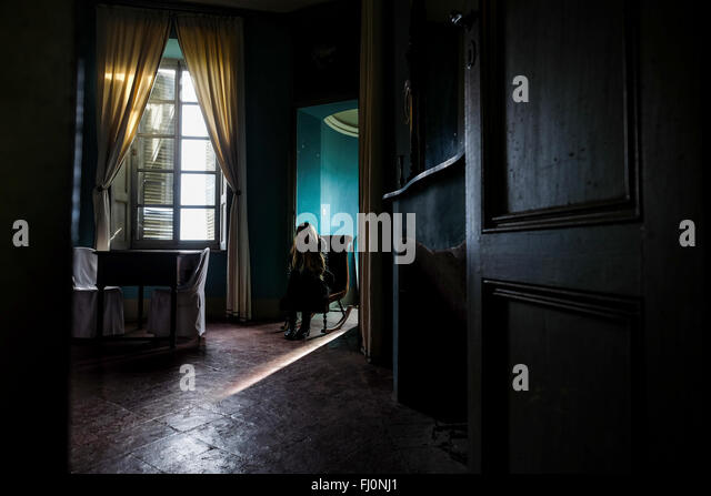 Young woman sitting in a gloomy room - Stock Image