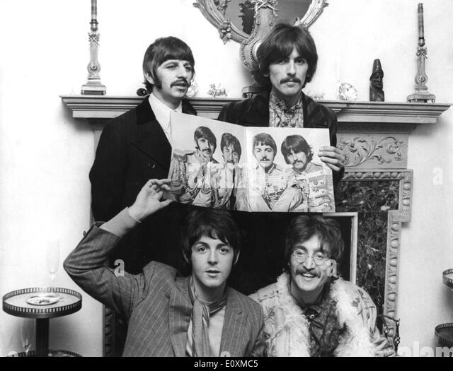 The Beatles Holding Up A Poster Of Themselves
