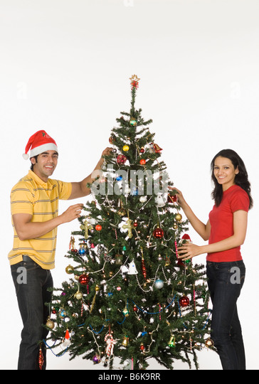 People Decorating For Christmas young couple decorating christmas tree stock photos & young couple