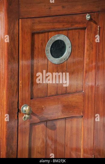 Door porthole window on old ship with reflected light of water on varnished wood & Door Porthole Window On Old Stock Photos \u0026 Door Porthole Window On ...
