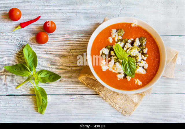 Tomato soup with feta cheese and pesto sauce in white bowl on wooden ...