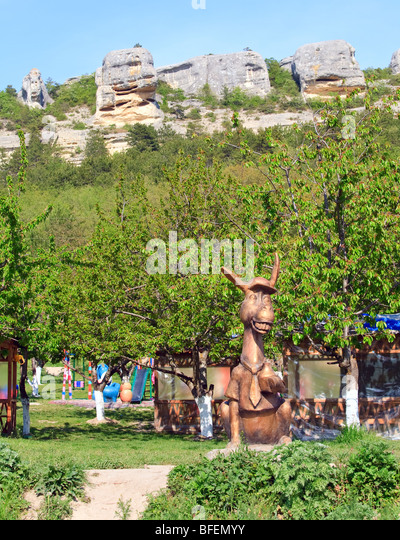 Copper Statue Of Donkey Near Spring Garden And Rocks Mountain Behind    Stock Image
