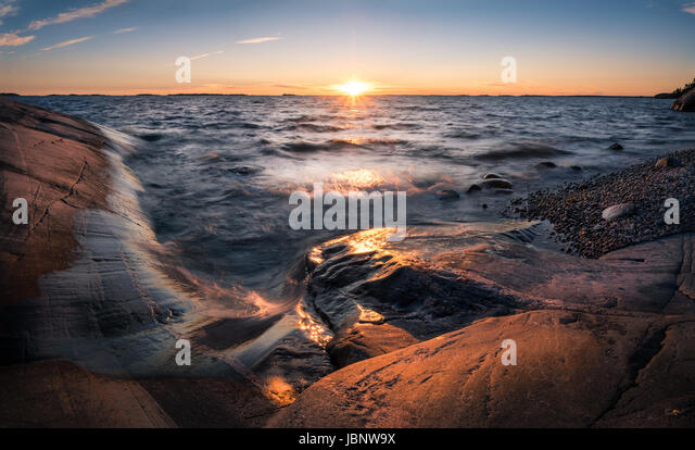 Scenic landscape with sunset and sea at summer evening in Finland - Stock Image