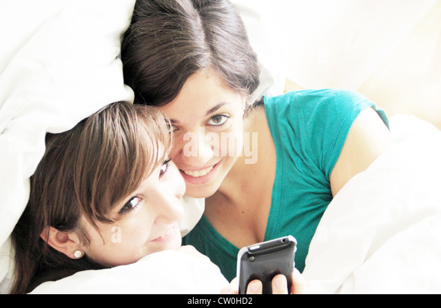 Teen girl bed phone stock photos teen girl bed phone for Cell phone bed