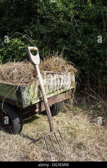 Antique Garden Tools On A Hay Filled Trailer.   Stock Image