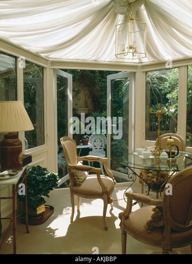 Conservatory Dining Room With Cream Ceiling Blinds And French Doors Open To Patio Garden