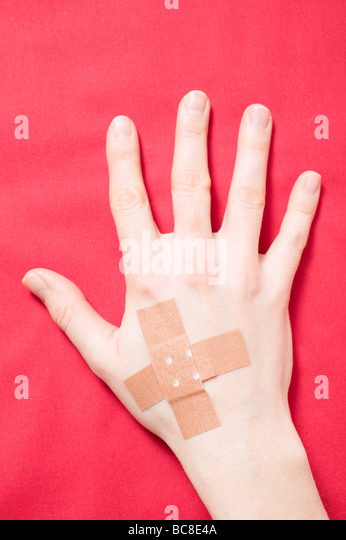 hand-with-crossed-sticking-plasters-overhead-view-bc8e4a.jpg