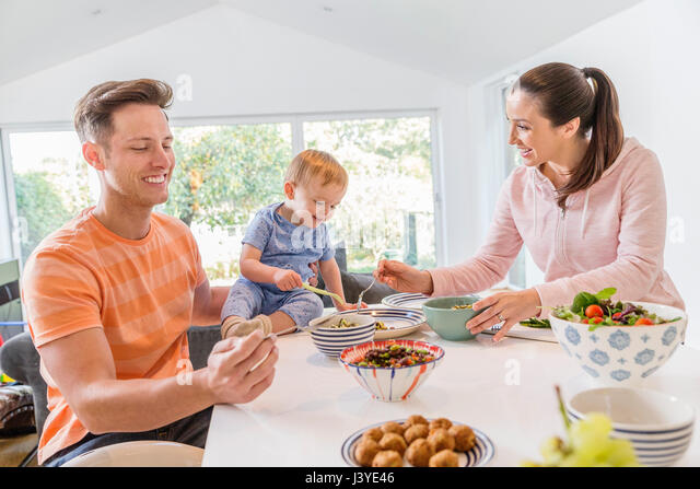 Young family having breakfast in the kitchen at home - Stock Image