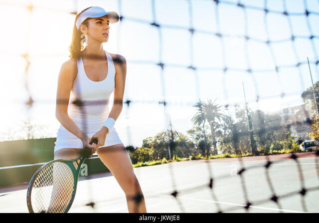 Portrait of a beautiful young tennis player with racket on court. Sportswoman playing a match on tennis court. - Stock Image