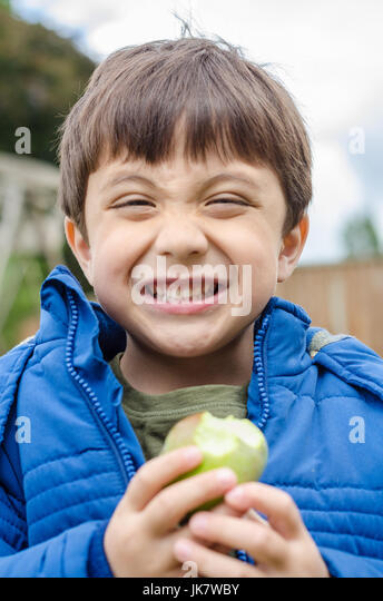 A boy eating a home grown apple in the back garden. - Stock Image