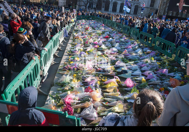 Crowds of people at Westminster placing bouquets in remembrance of the death of a police officer in terrorist attack - Stock Image