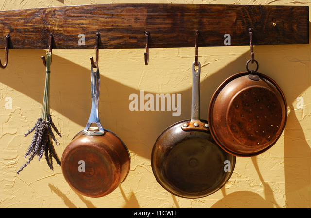 vintage copper pots and pans hanging from a wooden wine barrel rack on a stucco wall - Copper Pots