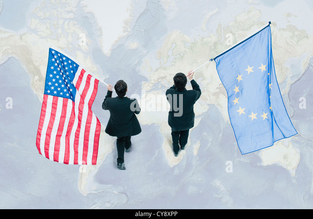 Businessman Walking On Top Of World Map Carrying American And European Union Flags Stock