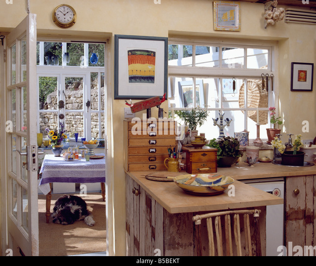 Picture Above Miniature Chest Of Drawers On Peninsular Unit In Rustic Cottage Kitchen With