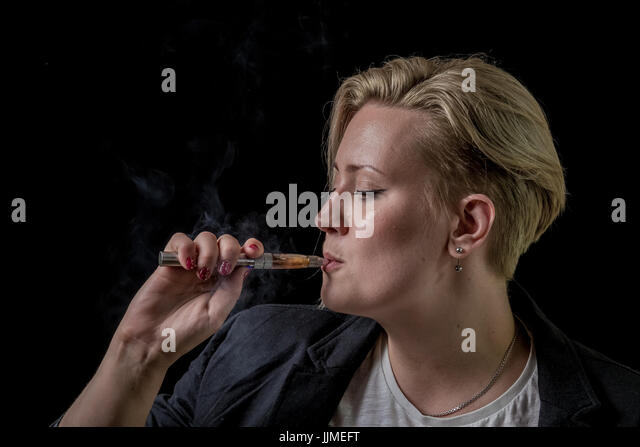 Young adult female inhaling smoke from electronic cigarette - Stock Image