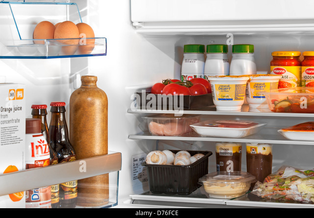 open refrigerator. cooled food and beverages in open fridge / refrigerator kitchen - stock image