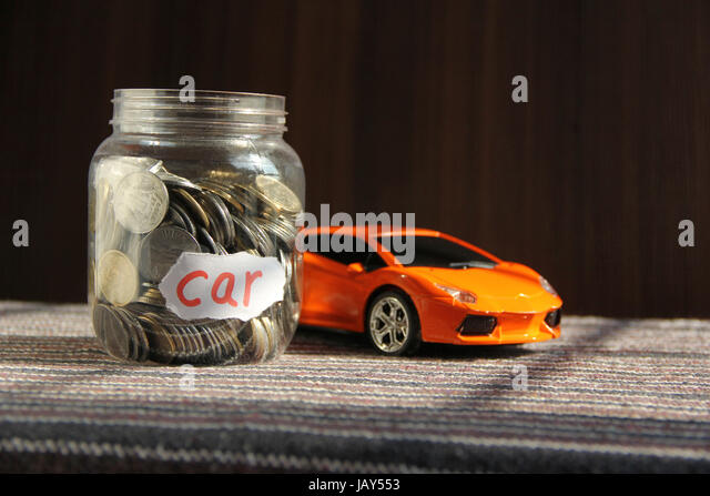 Coins in money jar with car label, finance concept - Stock Image