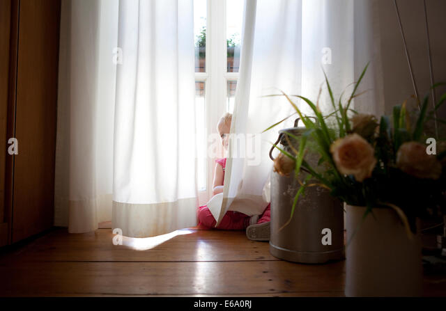young girl playing and peering out from behind opaque white curtains stock image