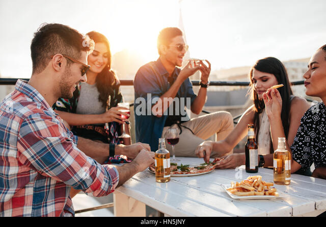 Group Of Young People Sitting Around And Eating Pizza Friends Partying