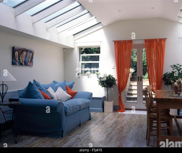 Blue Sofa And Orange Voile Drapes In Living Dining Room Extension With Wooden Flooring