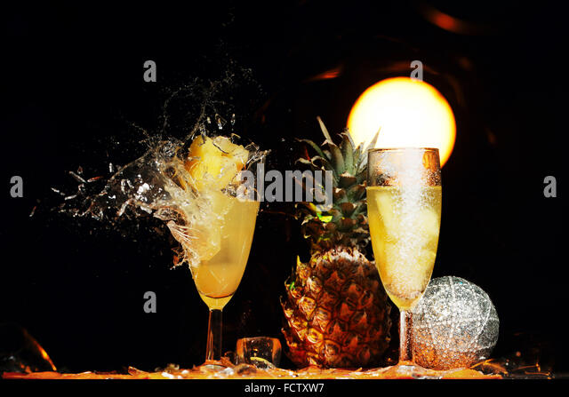 Shattering from gunshot champagne glasses with spilling liquid isolated on black - Stock Image
