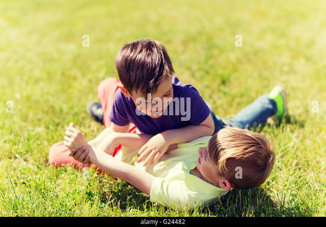 Happy Little Boys Fighting For Fun On Grass