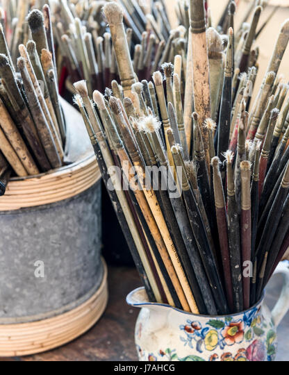 Artists paint brushes stored in jars - Stock Image