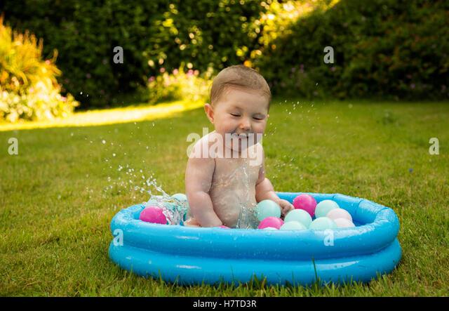 Paddling pool garden girl stock photos paddling pool for Baby garden pool