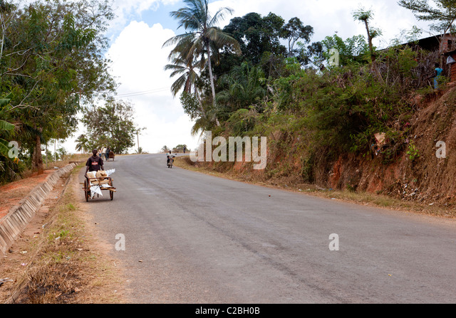 A Man Walking Down A Hill With A Push Cart Of Corrugated Tin Roofing.  Kisarawe