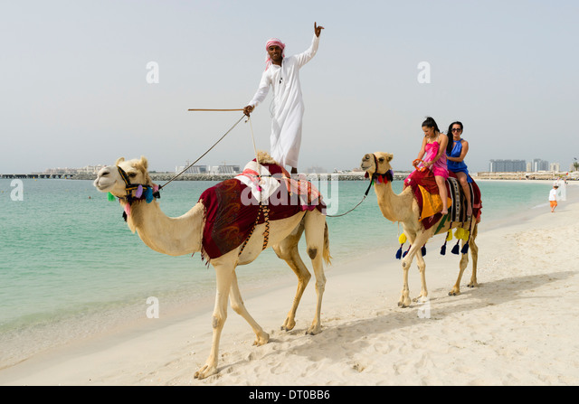 Camel riding dubai stock photos camel riding dubai stock images tourists taking a camel ride on beach at marina district of new dubai in united arab thecheapjerseys Images
