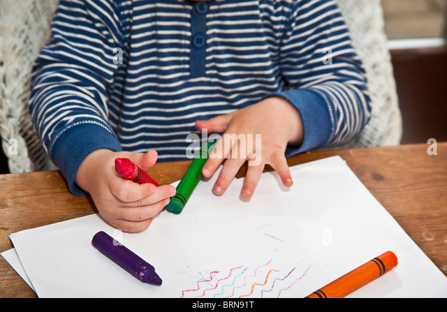 Child Coloring With Wax Crayons
